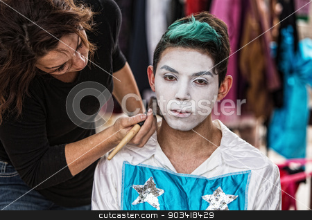 Woman Brushing Makeup on Clown stock photo, Makeup artist brushing white on serious young cirque performer by Scott Griessel