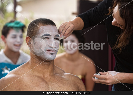 Young Performer Getting Makeup stock photo, Handsome young African-American circus performer getting makeup done by Scott Griessel