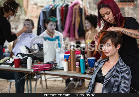 Fixing Performers' Hairdo stock photo, Makeup artist with red hair fixing young woman's hairdo by Scott Griessel
