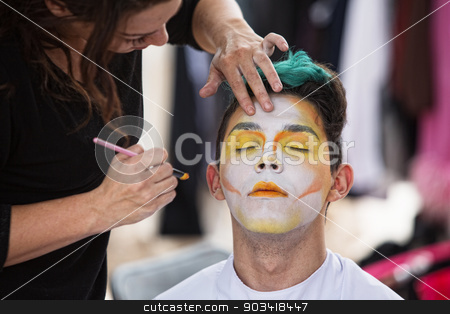Sylist Putting Makeup on Clown stock photo, Young male clown getting makeup on face by Scott Griessel