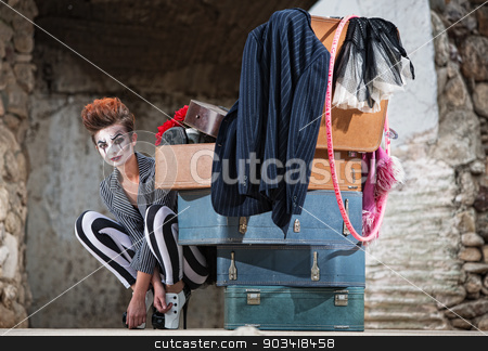 Grinning Clown Near Suitcases stock photo, Grinning female clown squatting near stack of suitcases by Scott Griessel