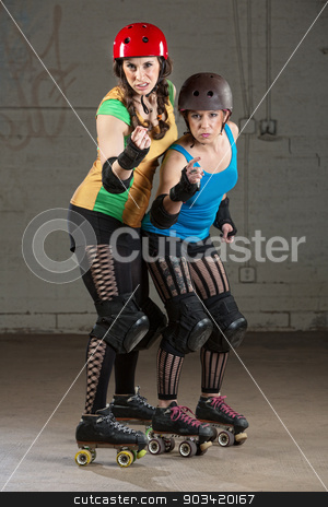 Roller Derby Skaters in Pointing Finger stock photo, Female roller derby skaters in helmets pointing and shaking fists by Scott Griessel