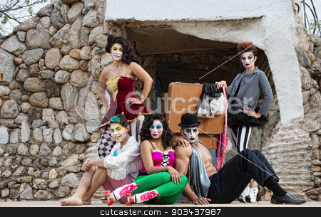 Cirque Performers on Stage stock photo, Group of male and female comedia del arte performers sitting on stage by Scott Griessel