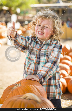 Cute Little Boy Gives Thumbs Up at Pumpkin Patch stock photo, Adorable Little Boy Leaning on Pumpkin Gives a Thumbs Up in a Rustic Ranch Setting at the Pumpkin Patch. by Andy Dean