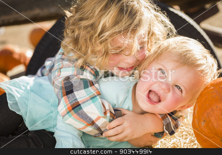Little Boy Playing with His Baby Sister at Pumpkin Patch stock photo, Sweet Little Boy Plays with His Baby Sister in a Rustic Ranch Setting at the Pumpkin Patch. by Andy Dean