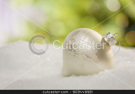 White Christmas Ornament on Snow Over an Abstract Background stock photo, Beautiful White Christmas Ornament on Snow Over an Abstract Background. by Andy Dean
