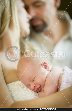Beautiful Young Couple Holding Their Newborn Baby Girl stock photo, Beautiful Young Couple Holding Their Newborn Sleeping Baby Girl Inside. by Andy Dean