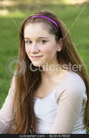 Grinning Teen Close Up stock photo, Grinning young female teenager sitting outside by Scott Griessel