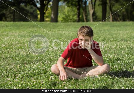Bored Teen Boy stock photo, Single bored teen boy sitting on grass by Scott Griessel