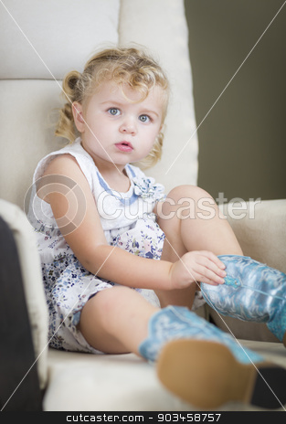 Blonde Haired Blue Eyed Little Girl Putting on Cowboy Boots stock photo, Adorable Blonde Haired Blue Eyed Little Girl Putting on Cowboy Boots. by Andy Dean