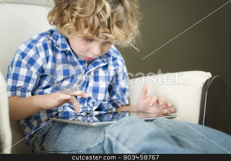 Young Blond Boy Using His Computer Tablet stock photo, Cute Young Blond Boy Using His Computer Tablet in a Chair. by Andy Dean