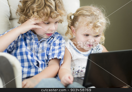 Young Brother and Sister Using Their Computer Laptop Together stock photo, Adorable Young Brother and Sister Using Their Computer Laptop Together. by Andy Dean