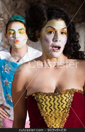 Embarrassed Female Clown stock photo, Embarrassed female cirque clown and man blowing kisses by Scott Griessel