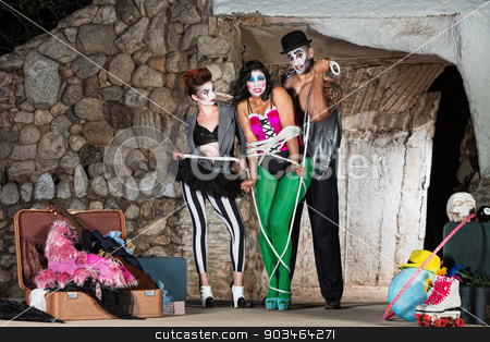 Cirque Clowns Tying Up Friend stock photo, Group of cirque clowns tying up woman with rope by Scott Griessel