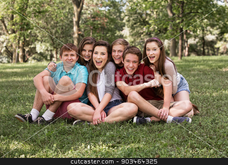 Happy Group Sitting Outdoors stock photo, Happy group of European teenagers sitting on grass by Scott Griessel