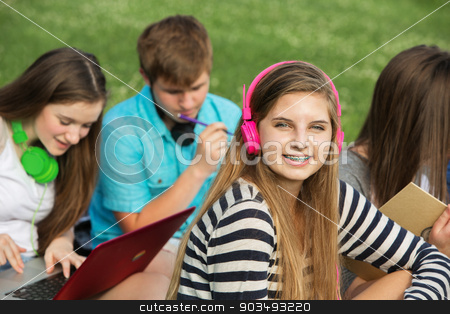 Smiling Girl with Pink Headphones stock photo, Smiling cute teen girl with braces and pink headphones by Scott Griessel