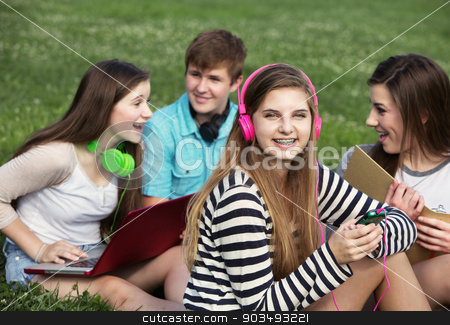 Cute Girl with Braces stock photo, Cute teen with friends sitting outdoors on lawn by Scott Griessel