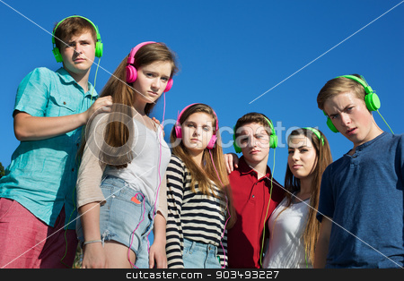 Frowning Teenagers stock photo, Group of offended teens in pink and green headphones by Scott Griessel