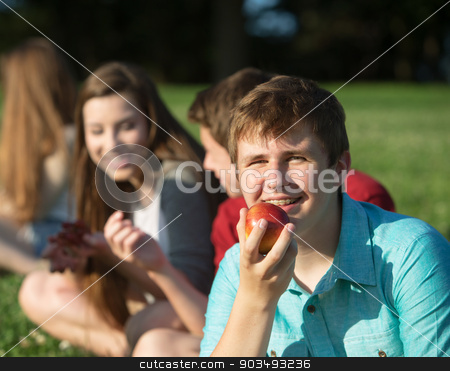 Happy Teen Eating Fruit stock photo, Happy young person with friends holding fruit by Scott Griessel