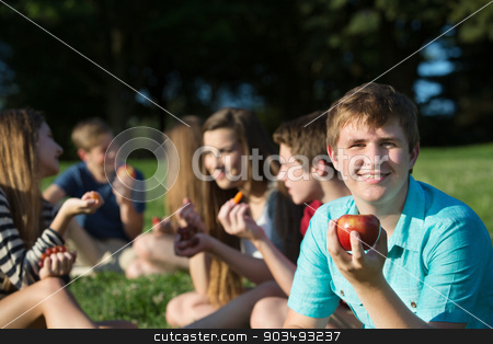 Teen Male Holding an Apple stock photo, Cute European teen boy with friends holding apple by Scott Griessel