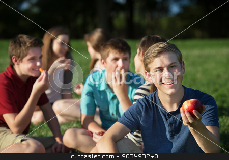 Cheerful Teen Holding Apple stock photo, Smiling male teenager with friends holding apple by Scott Griessel