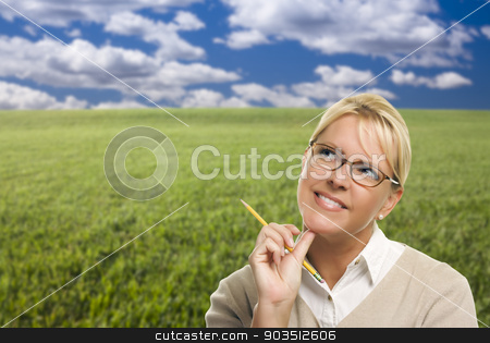 Contemplative Woman in Grass Field Looking Up and Over stock photo, Contemplative Woman in Grass Field Looking Up and Over to the Side. by Andy Dean