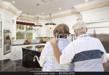 Senior Couple Looking Over Beautiful Custom Kitchen stock photo, Happy Senior Couple Looking Over Beautiful Custom Kitchen Design. by Andy Dean