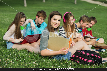 Smiling Student with Friends stock photo, Smiling student with binder and group of friends outdoors by Scott Griessel