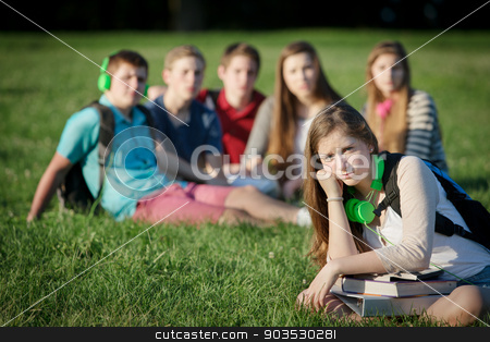 Lonely Teen with Group stock photo, Lonely female teen student sitting near group by Scott Griessel