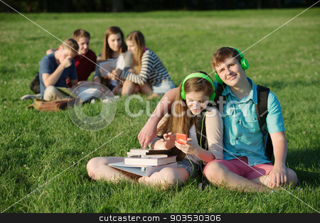 Cute Teen Couple with Headphones stock photo, Cute student teen couple listening to music outdoors by Scott Griessel