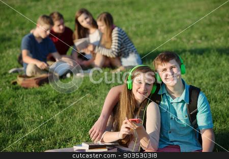 Cute Teens with Earphones stock photo, Pair of cute teens with cell phone and earphones by Scott Griessel