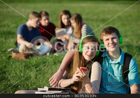 Two Teen Students with Headphones stock photo, Two teenage students sitting outdoors with earphones by Scott Griessel