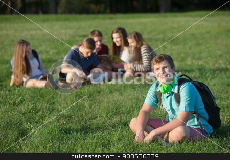 Handsome Teen with Backpack stock photo, Handsome European teen male student sitting on lawn by Scott Griessel