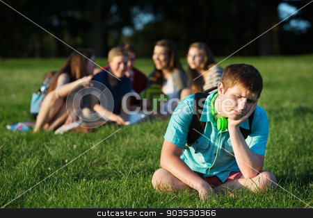 Group Bullying Teen stock photo, Group of teen bullying sad student sitting outdoors by Scott Griessel