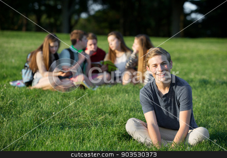 Cheerful Smiling Teen stock photo, Cheeful smiling teen male near group outdoors by Scott Griessel