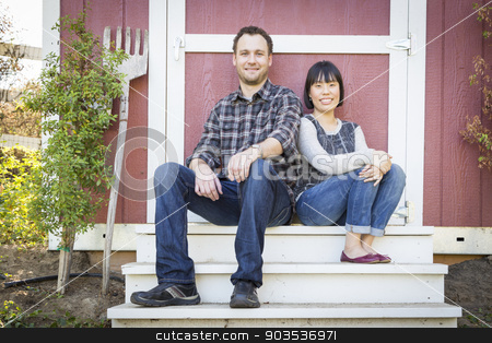 Mixed Race Couple Relaxing on the Steps stock photo, Happy Mixed Race Couple Relaxing on the Steps of Their Barn. by Andy Dean