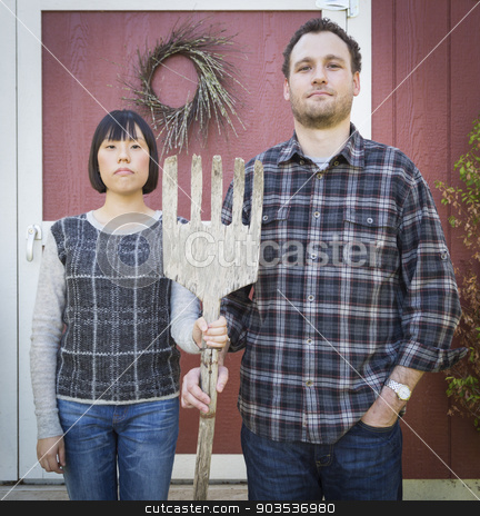 Fun Mixed Race Couple Portrait Simulating the American Gothic Pa stock photo, Fun Mixed Race Couple Portrait Simulating the American Gothic Painting by Grant Wood. by Andy Dean