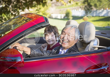 Happy Chinese Couple Enjoying An Afternoon Drive in Their Conver stock photo, Attractive Happy Chinese Couple Enjoying An Afternoon Drive in Their Convertible. by Andy Dean