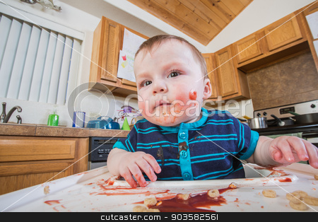 Messy Child Eats stock photo, A messy child eats breakfast in the kitchen by Scott Griessel