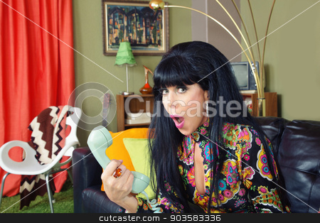 Embarrassed Lady on Phone stock photo, Embarrased single 1960s woman on sofa holding telephone by Scott Griessel