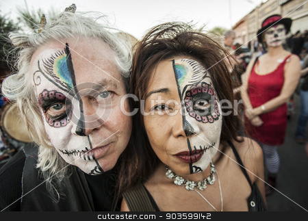 Couple on Dia De Los Muertos in Makeup stock photo, TUCSON, AZ/USA - NOVEMBER 09: Two unidentified people wearing facepaint at the All Souls Procession on November 09, 2014 in Tucson, AZ, USA. by Scott Griessel