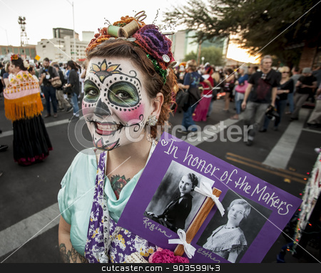 Woman with Sign in Dia De Los Muertos Makeup stock photo, TUCSON, AZ/USA - NOVEMBER 09: Unidentified woman with memorial sign in facepaint at the All Souls Procession on November 09, 2014 in Tucson, AZ, USA. by Scott Griessel