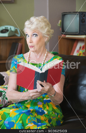 Impressed Book Reader stock photo, Impressed senior woman in 1970s fashion holding book by Scott Griessel
