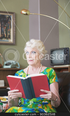 Skeptical Woman with Book stock photo, Single skeptical woman in green reading a book by Scott Griessel