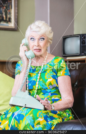 Cringing Lady on Phone stock photo, Cringing pretty senior woman in green on telephone by Scott Griessel
