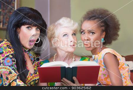 Women Reading a Romance Novel stock photo, Diverse beautiful mature women reading a romance novel by Scott Griessel