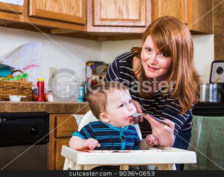 Woman Feeds Baby in Kitchen stock photo, A woman feeds her baby juice in the kitchen by Scott Griessel