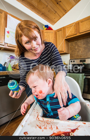 Woman Feeds Her Gumpy Baby stock photo, Grumpy baby in kitchen is being fed from her bottle by Scott Griessel
