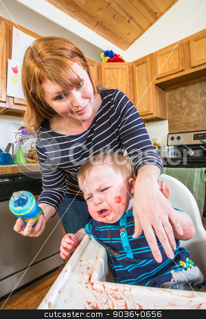 Woman Feeds Gumpy Baby stock photo, Grumpy baby in kitchen is being fed from bottle by Scott Griessel