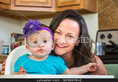 Mother Smiles With Baby stock photo, Mother in messy kitchen smiles as baby eats by Scott Griessel